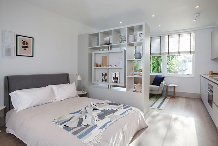 aménagement petit appartement avec lit gris et blanc séparée d un petit coin sejour avec canapé gris, cuisine blanche avec plan de travail noir