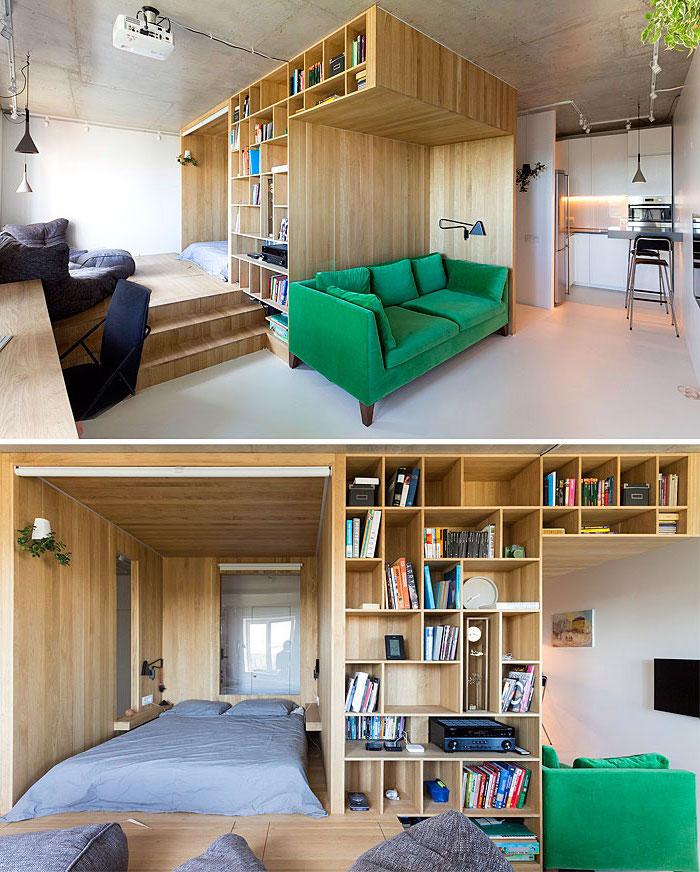 idée déco studio avec lit dans une niche de vois meuble bibliotheque, canapé vert foncé, bureau bois, décoration appartement étudiant avec kitchenette studio blanche