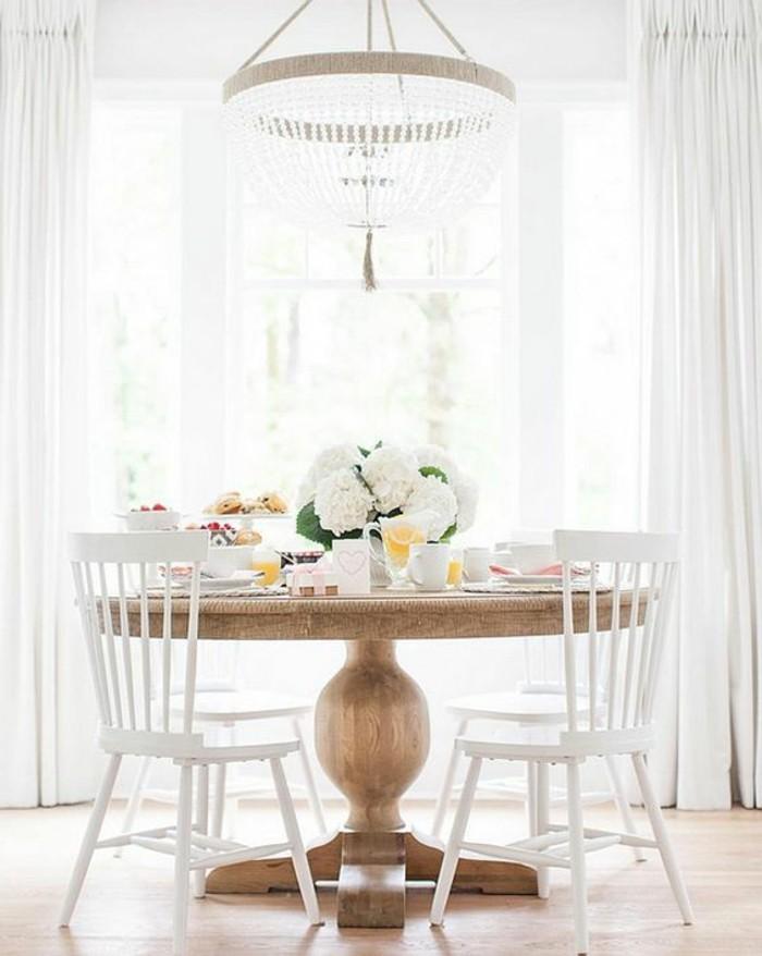 originale-table-de-cuisine-en-bois-clair-chaises-en-bois-blanches-fleurs-sur-la-table-fenetre