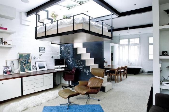 lit suspendu en hauteur avec matelas blanc et linge de lit blanc, escalier avec mur peinture à la craie, bureau bois long, salle à manger petite à coté d une baignoire salle de bain
