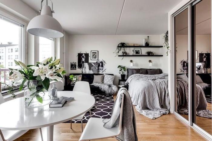 idée déco studio gris et blanc avec des murs blanc et petit coin repas avec chaises et table blanche, parquet bois clair