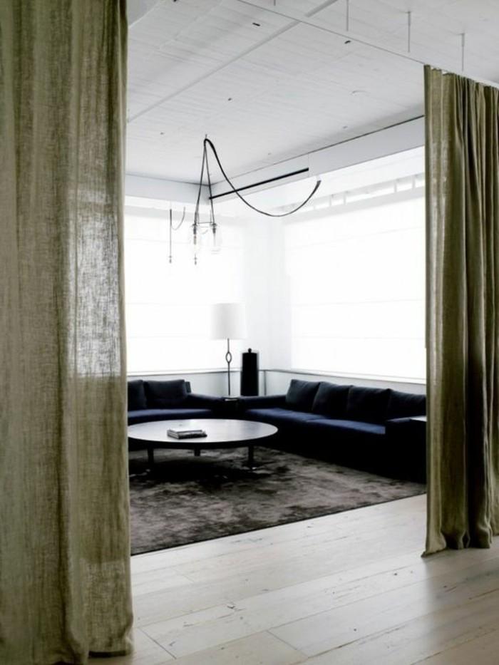 séparation-de-pièce-amovible-salon-sol-en-parquet-clair-tapis-marron-foncé-canapé-d-angle-bleu
