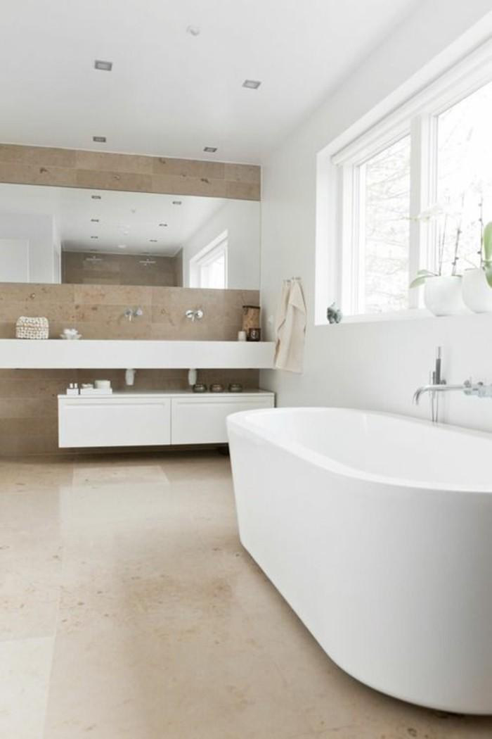 salle-de-bain-taupe-baignoire-blanche-grande-sol-en-dalles-beiges-miroir-mural