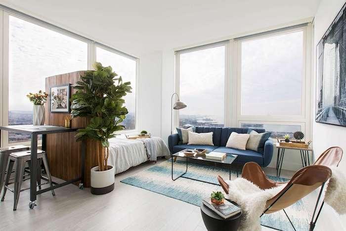 comment aménager un studio avec canapé bleu marine et lit blanc, chaise en cuir, tapis bleu et blanc, table et tabourets industriels