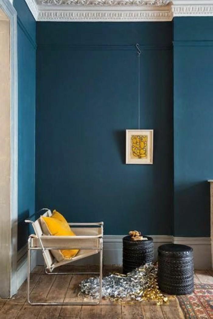 salon-murs-en-bleu-foncé-canape-beige-sol-en-planchers-bois-tapis-coloré-chaises-basses-en-rotin