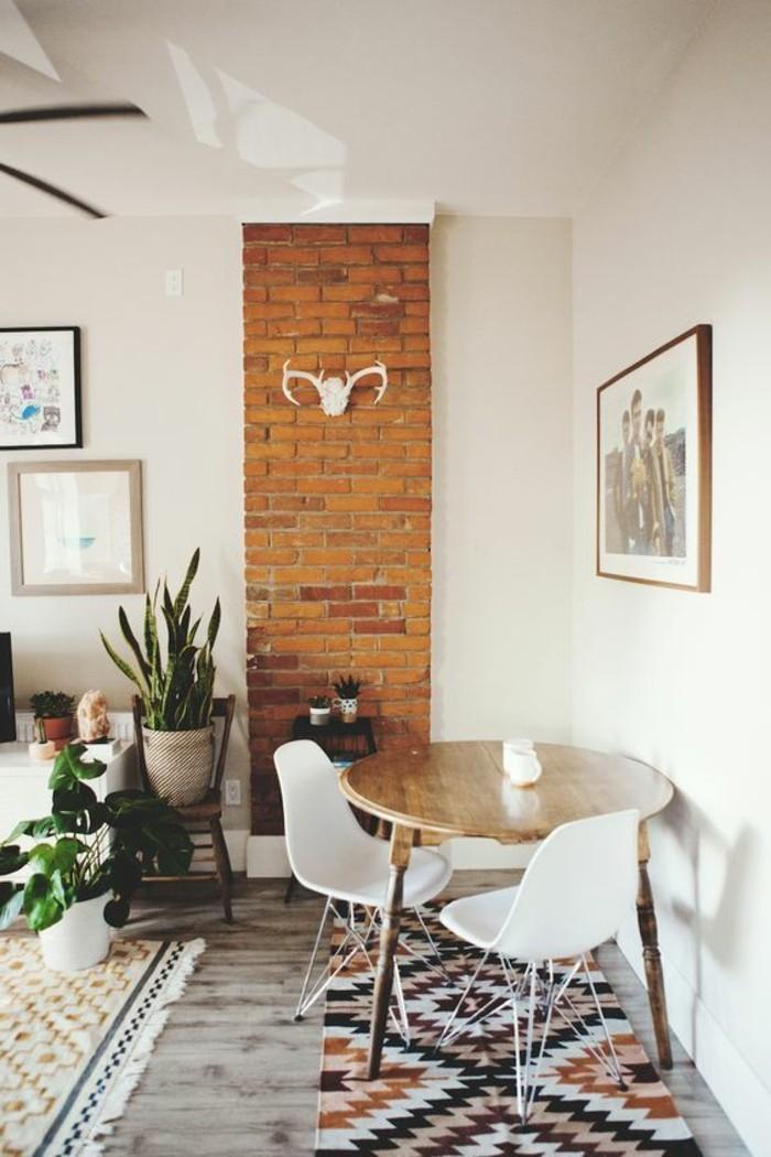 sol-en-parquet-tapis-coloré-mur-en-briques-mur-beige-table-en-bois-chaises-en-plastique-blanche
