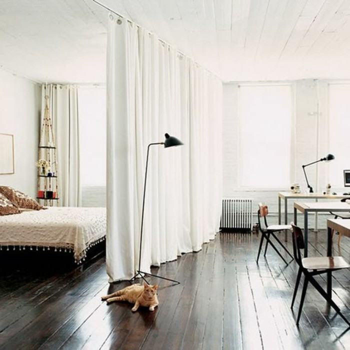 studio-rideau-séparation-chambre-rideau-blanc-sol-en-planchers-bois-foncé-murs-blancs