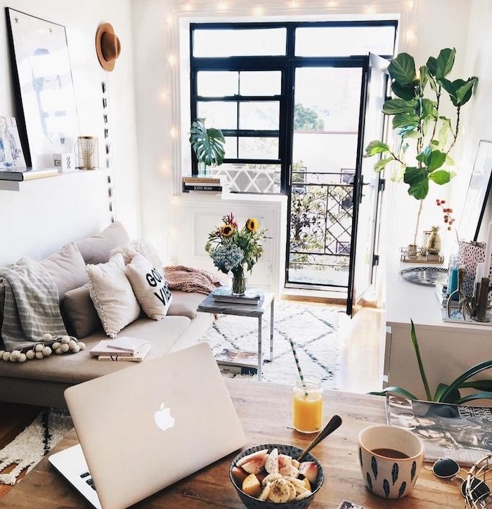 exemple aménagement studio avec canapé gris décoré de coussins boheme chic et un meuble tv en face, murs blancs, table salle à manger avec petit dejeuner sain