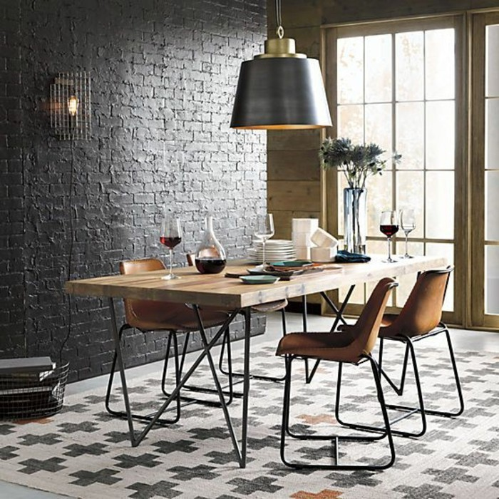 table-en-bois-et-fer-noir-mur-en-briques-noirs-lustre-suspendu-tapis-beige-noir