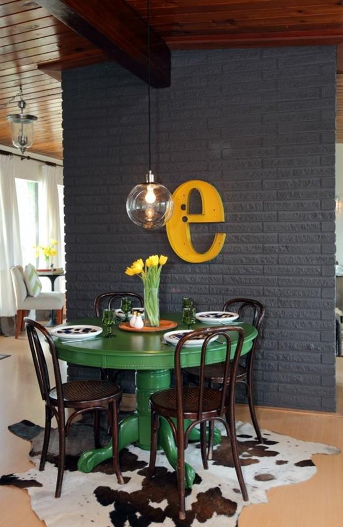 table-en-bois-rond-peint-en-vert-decoration-murale-avec-lettres-mur-en-briques-gris