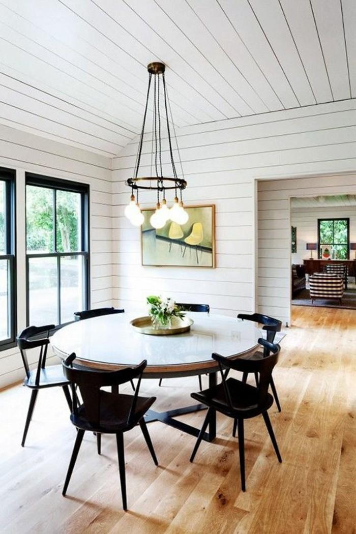 table-ronde-sol-en-parquet-clair-chaises-en-bois-chaise-noire-lustre-en-fer