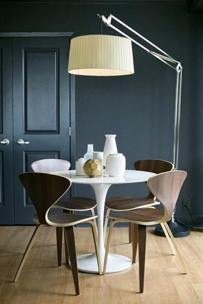 table-tulipe-blanche-en-plastique-sol-en-parquet-clair-chaise-en-bois-foncé-salle-de-sejour-bleu-foncé