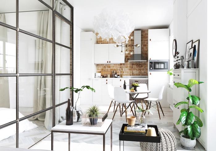 kitchenette studio blanche avec credence cuisine mur de briques, meuble cuisine blanc, coin repas avec table et chaises scandinaves, coin salon avec table blanc et metal, pouf tressé