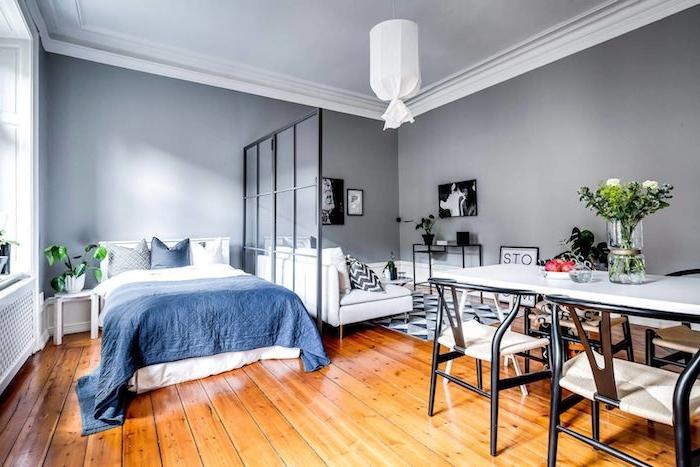 améangement petit appartement avec salle à manger, chambre avec linge de lit bleu et blanc, verrière de séparation à coté d un salon gris et blanc