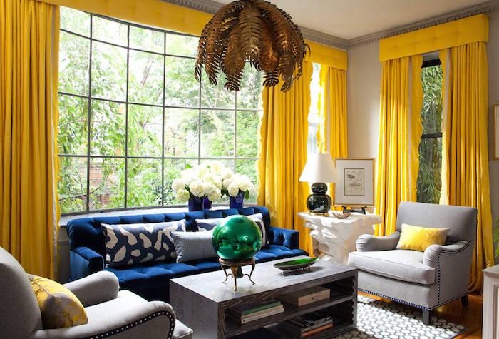 idée d association de couleur avec le gris, mur couleur grise, rideaux jaunes, canapé bleu marine, table basse bois marron et suspendion originale dorée