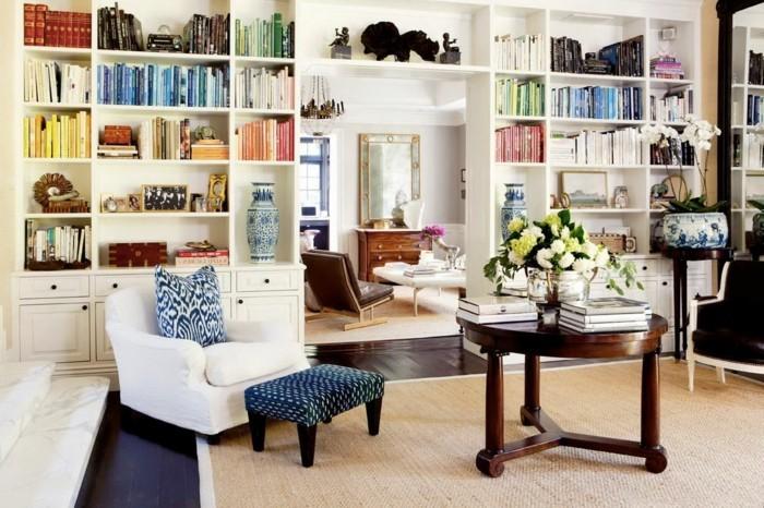 idée-déco-petit-salon-grande bibliothèque qui délimite l'espace, guéridon en bois massif, fauteuil blanc minimaliste, ambiance accueillante