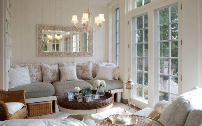 idée-déco-petit-salon-ambiance-romantique-grand-canapé-coussins-à-motifs-floraux-table-basse-fauteuil-en-rotin-grand-miroir-réflecteur