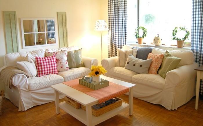 idée-déco-petit-salon-décor-sympa-et-romantique-tables-basse-avec-espace-de-rangement-coussins-colorés-sofas-blancs