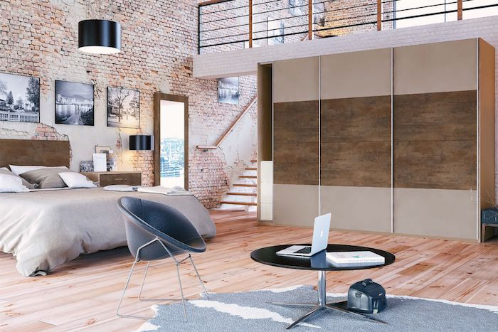 quelle couleur associer au gris, linge de lit et tapis gris, parquet clair, mur en briques, tete de lit et portes dressing marron, coin de travail gris et noir