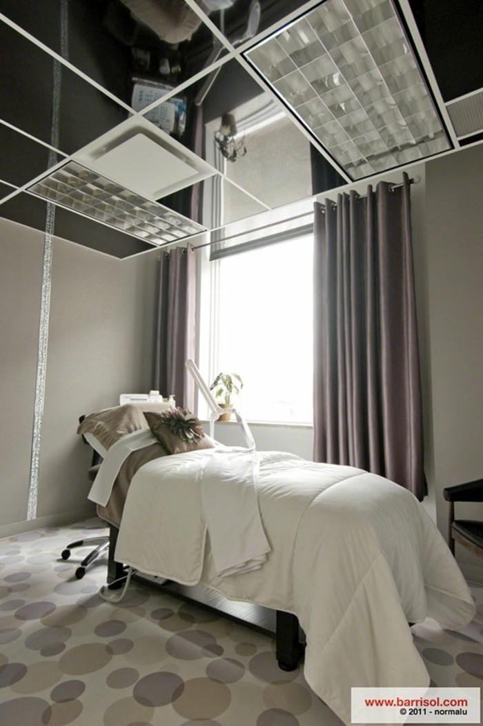 idee-deco-plafond-dalles-lumineuses-sol-en-moquette-beige-fenetre-grande-rideaux-violettes