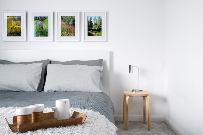 quelle couleur associer au gris, linge de lit gris et blanc, murs couleur blanche, table de nuit bois et deco murale de cadres, photos paysages naturels