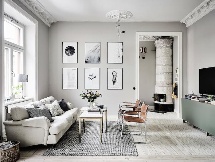 intérieur aux murs repeints de peinture grise, cheminée design, canapé blanc et chaises marron cuir, tapis gris, meuble tv vert de gris