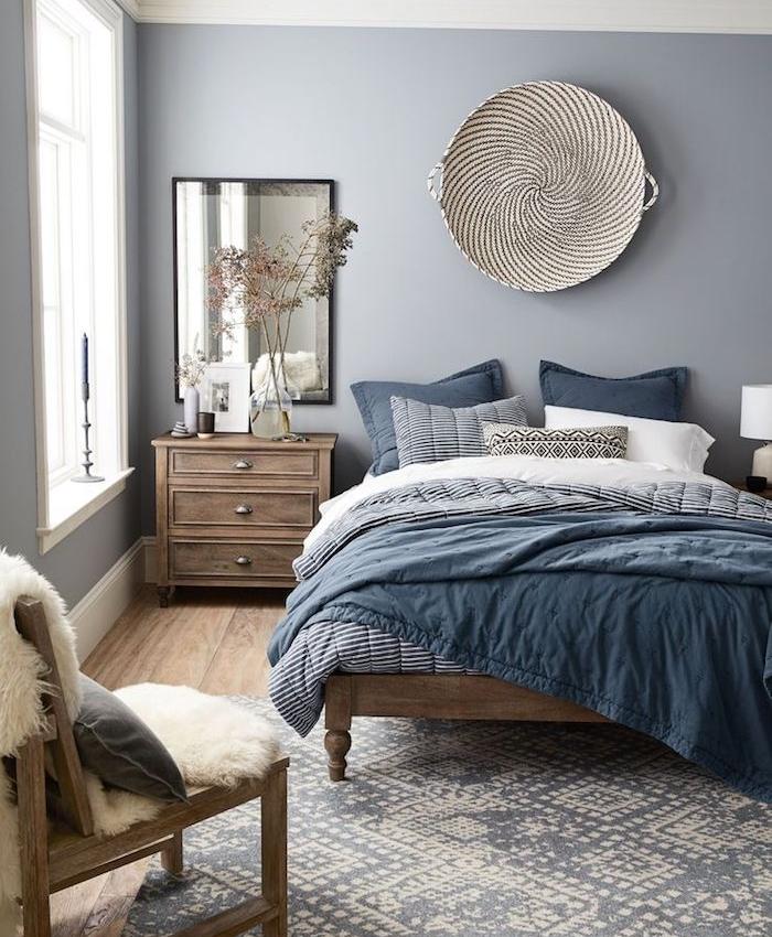 chambre à coucher décorée de peinture grise, linge de lit gris, blanc et bleu, deco murale orientale, meubles en bois marron