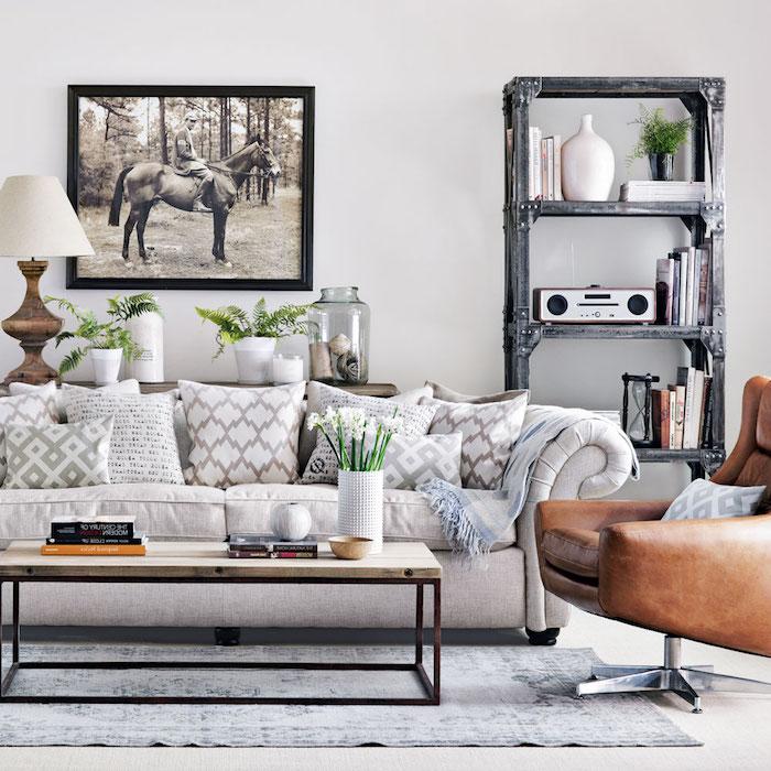 peinture grise murale dans un salon avec canapé gris perle, fauteuil marron en cuir, table basse bois et metal, etagere bibliotheque industrielle