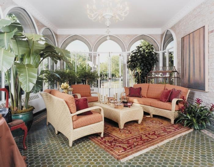 aménagement-veranda-en-coin-de-repos-déco-composée-de-nombreuses-plantes-exotiques-canapé-en-rotin-sièges-oranges-table-à-café-marron-tapis-exotique-lustre-somptueux