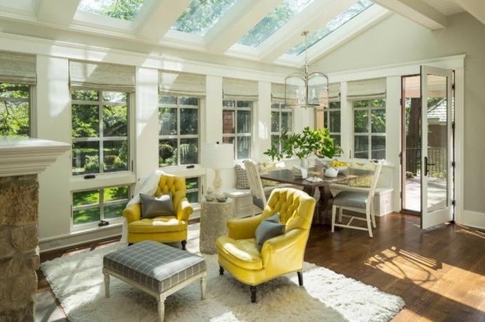 deco-veranda-traditionnelle-coin-repas-et-coin-détente-deux-canapés-jaunes-qui-contrastent-sur-le-fond-blanc
