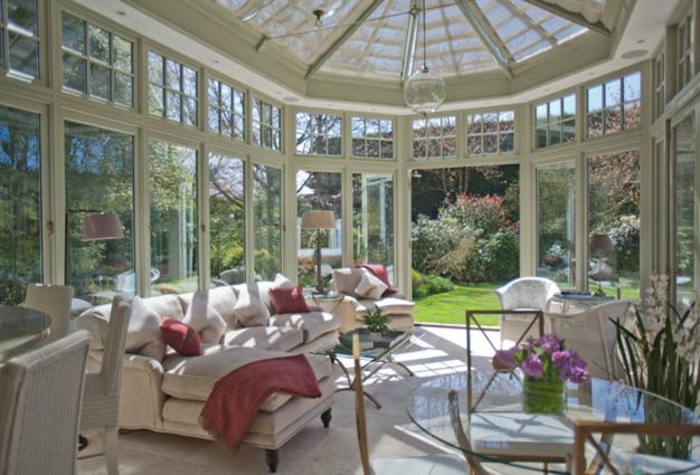 verrière-extérieure-blanche-amenagement-veranda-élégant-gros-canapé-table-en-verre-chaises-en-rotin-déco-impressionnante