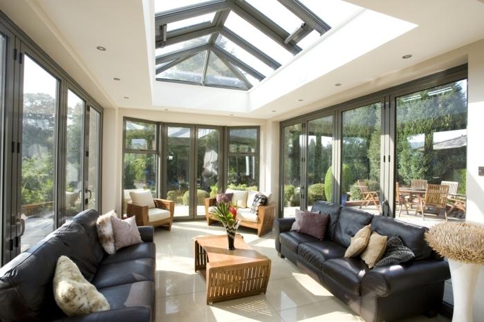 verrière-extérieure-carrelage-canapés-noirs-meubles-en-bois-ambiance-chaleureuse