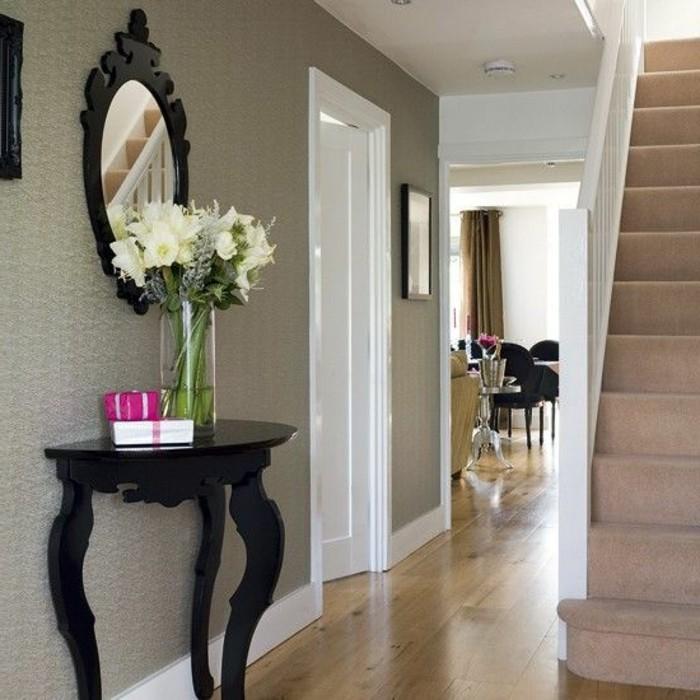 105-Tapisserie couloir. Un miroir. Une table. Un escalier.
