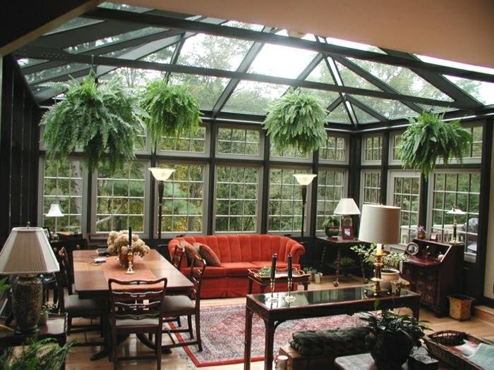 verrière-extérieure-noire-aménagée-avec-de-meubles-en-bois-un-joli-sofa-contrastante-végétation-qui-surplombe-le-décor-vintage