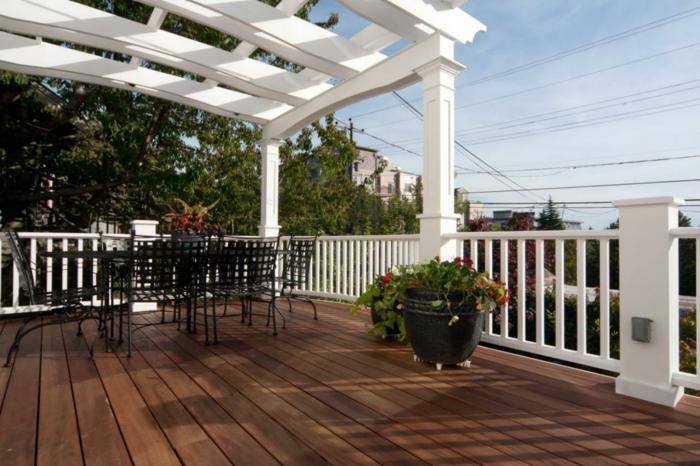 pergola-terrasse-blanche-qui-accueille-un-coin-repas-chaises-et-table-noires