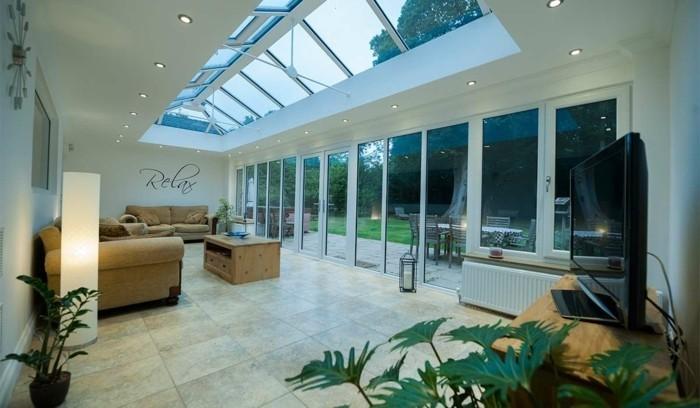 veranda-moderne-aménagée-en-salon-un-espace-propice-à-la-relaxation-deux-canapés-confortables-une-petite-tables-en-bois-veranda-spacieuse-toit-veranda-en-verre