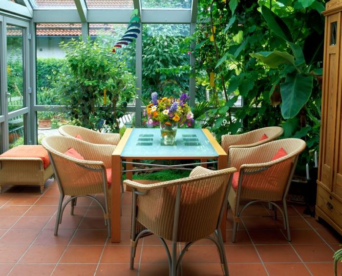 amenagement-veranda-en-salle-à-manger-meubles-en-rotin-table-en-verre-et-bois-veranda-florale