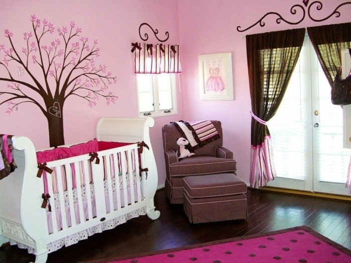 deco-chambre-bebe-fille-en-rose-douceur-et-apaisement-déco-murale-à-motifs-floraux-lit-bébé-blanc-fauteuil-marron