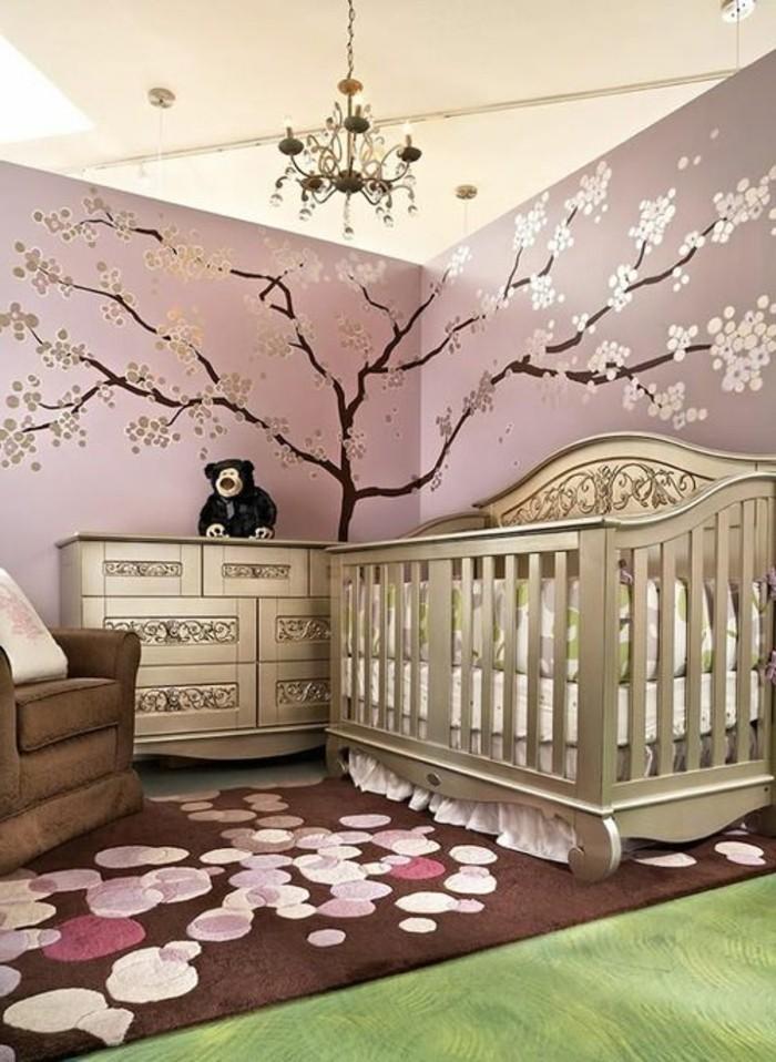 deco-chambre-bebe-fille-rose-avec-une-jolie-déco-murale-arbre-commode-et-lit-à-barreaux-couleur-or-fauteil-marron-tapis-marron