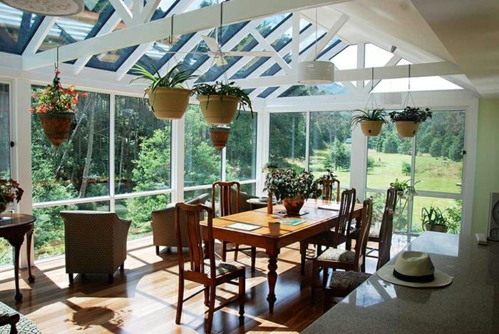 formidable-idee-deco-veranda-aménagée-en-salle-à-manger-une-abondance-de-plantes-sol-stratifié-vue-sur-un-paysage-forestier