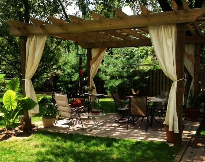pergola-de-jardin-en-bois-aménagement-en-chaises-et-table-un-paysage-vert