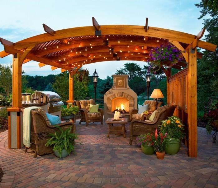 magnifique design pergola-en-bois-parée-de-lumières-et-de-nombreuses-plantes-meubles-en-rotin-et-une-cheminée-qui-crée-une-ambiance-romantique
