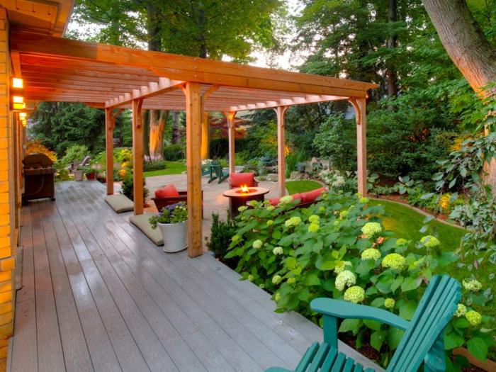 pergola-en-bois-adossée-à-une-maison-en-bois-pergola-contemporaine-cernée-de-toute-part-de-végétation-espace-détente-aménagée-avec-des-chaises-longues