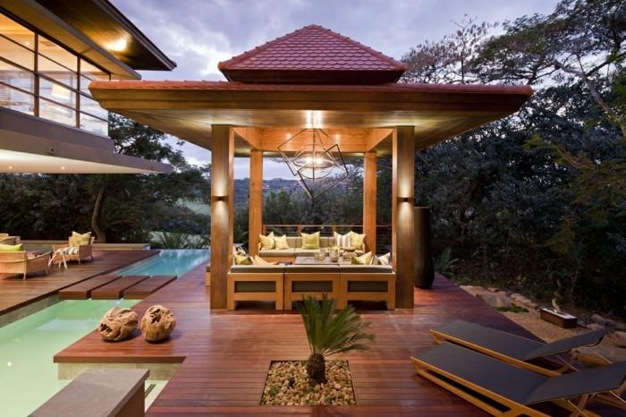 pergola-en-bois-type-gazebo-qui-accueille-un-coin-détente-et-loisir-situé-près-de-la-piscine-un-éclairage-romantique