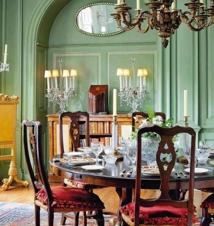 decoration-salle-à-manger-verte-ambiance-exquise-lustre-impressionnantes-table-en-bois-chaises-en-bois-à-sièges-rouges
