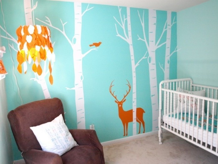 peinture-chambre-bébé-à-jolis-motifs-sur-un-fond-bleu-canapé-marron-lit-à-barreaux-blanc