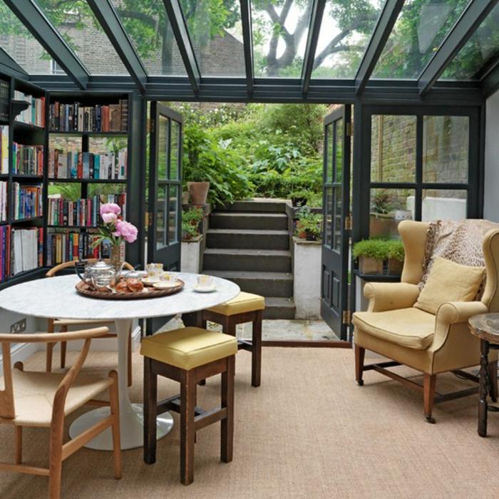 deco-veranda-aménagée-en-coin-détente-bibliothèque-table-et-chaises-en-bois-joli-fauteuil-vintage-le-meilleur-espace-pour-s-adonner-à-la-lecture
