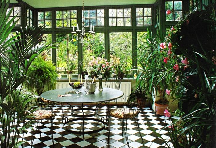 deco-veranda-aménagée-en-jardin-d-hiver-intérieur-veranda-plongée-dans-la-verdure-table-ronde-des-chaises
