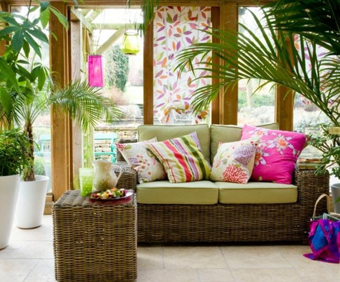 deco-veranda-dans-un-style-tropical-aménagée-avec-beaucoup-de-plantes-meubles-en-rotin-coussins-multicolores