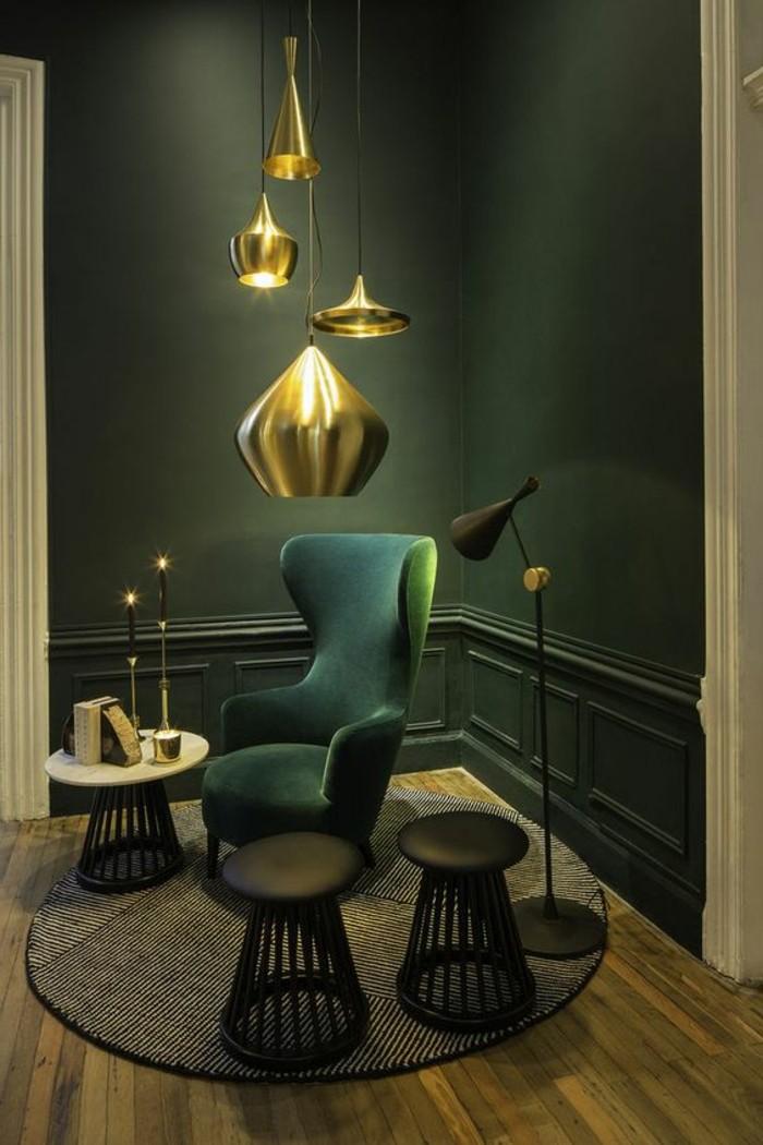 lampe-en-or-tapis-rond-chaise-en-bleu-foncé-sol-en-parquet-mur-vert-eclairage-intérieur
